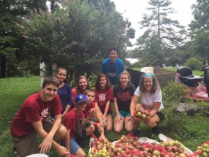 Eight 4-H club members and the apples they gleaned to give to the food bank