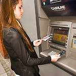 Image of teenage girl at ATM cash point machine withdrawing money
