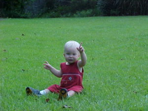 child playing in grass