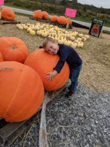 Child leaning on pumpkin