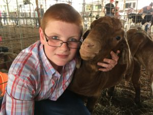 Austin Taylor holding one of his brown goats