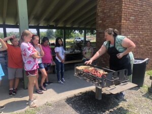 Woman grilling and talking to kids